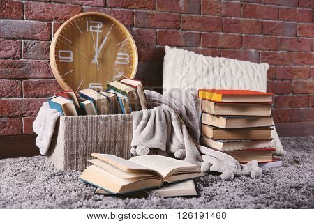 Pile of books in box and clock on brick wall background
