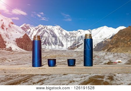 Two Blue Thermoses and Cups on Wooden Table with Beautiful Himalaya Mountains and Clear Blue Sky Shining sun on Background Active Lifestyle Concept