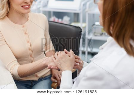 Everything will be okay. Experienced doctor is supporting her patient. She is sitting and holding a female hand. The women are smiling