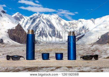 Active Lifestyle Couple Concept Two Blue Travel Thermoses Cups and Sunglasses on Wood Table and Mountain Landscape Focus on Thermoses