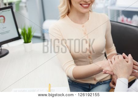 Do not worry. Professional general practitioner is holding female hand with support. The young woman is sitting and smiling