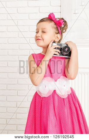 little girl hugging a retro camera eyes shut