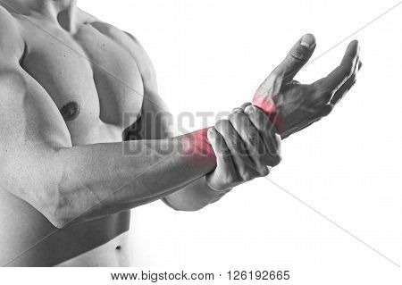 young man with strong muscle body holding with hand his damaged wrist suffering pain in sport injury and health care concept isolated on black and white with red spot sore area