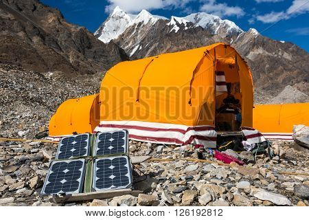 Solar Battery on Rocky Glacier Moraine for Electricity Supply of Sport Mountain Expedition in Wilderness Country with Camping Tents on Background