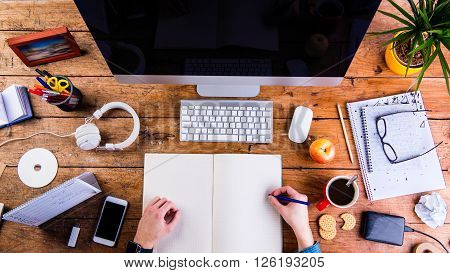 Business person working at office desk, writing into a notebook. Smart phone on the table. Copy space. Flat lay.