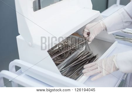 Close up of arms of female gynecologist talking medical instrument from the set. The woman is standing and wearing sterile gloves