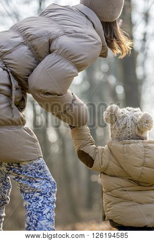 View from behind of young mother leaning to her toddler child pointing at something up in the air as they walk through the nature wearing winter coats.