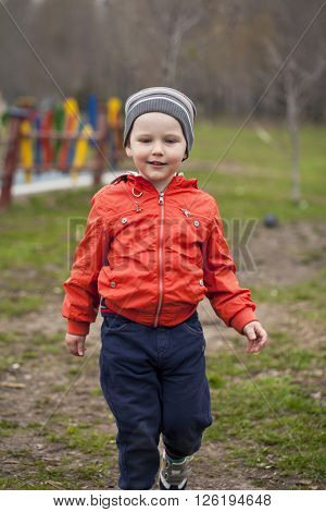 Close up portrait of a beautiful baby boy walking in spring park. Little boy in orange jaket and blue jeans, outdoors