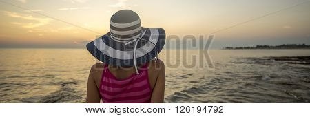 View from behind of a woman wearing striped straw hat looking at the ocean under the evening sky.