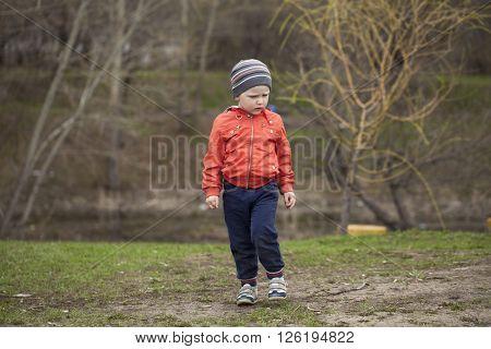 Full length portrait of a beautiful baby boy walking in spring park. Little boy in orange jaket and blue jeans, outdoors