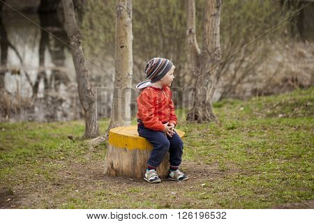 Close up portrait of a beautiful baby boy walking in spring park. Little boy in orange jacket, outdoors