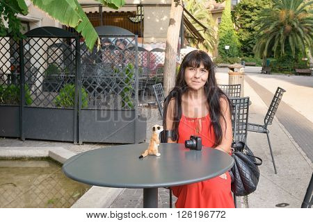 nice girl sitting on a chair at a little iron table with a puppet on it