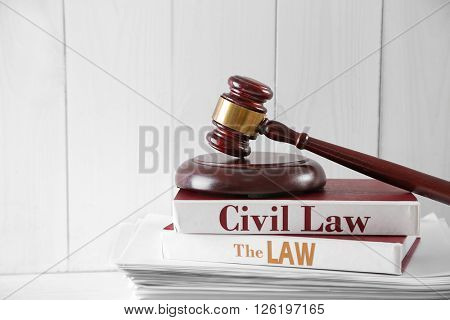 Gavel on stack of paper and books books on wooden background