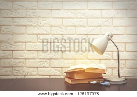 Modern lamp and books on the desk on white wall background