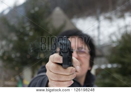 Woman shooting outdoor with a gun,  selective focus after shoot the Pistol.