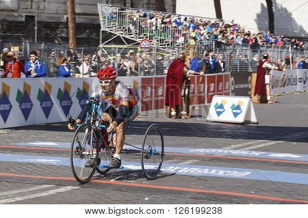 Rome Italy - April 10 2016: An athlete in hand bike race arrives at the finish line and cheers for the challenging test passed.