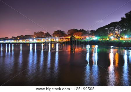 Lower Seletar Reservoir (in the north of Singapore) with light reflections from park connector under reddish and purplish night sky