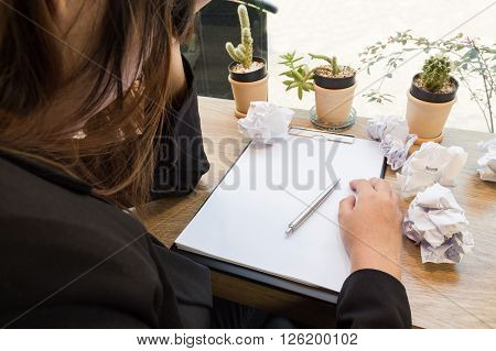 Stressed woman sitting at wooden desk with paper balls.