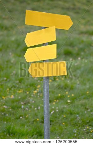 Blank direction signs against clear blue sky