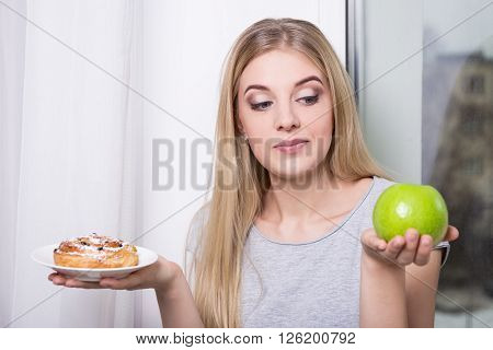 Diet Concept - Woman Choosing Behind Pastry And Green Apple