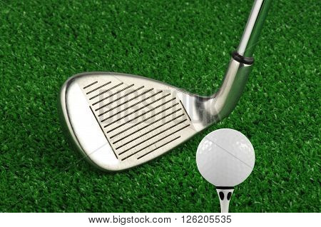 Golf Iron club tee off on green