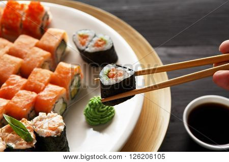 Eating sushi rolls. Japanese food restaurant, sushi maki gunkan roll plate or platter set. Closeup of hand with chopsticks taking roll. Ginger, soy, wasabi. Sushi at black rustic wood background.
