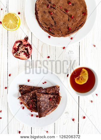 Chocolate crepes or pancakes with oatmeal and pomergranate. White wood table with healthy homemade sugar and eegs free breakfest dish on white plate, with a cup of tea with lemon and pomegranate near