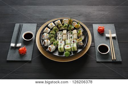 Japanese food restaurant, sushi maki gunkan roll plate or platter set. Set for two with chopsticks, ginger, soy, wasabi. Sushi at rustic wood background and black stone. POV at black.
