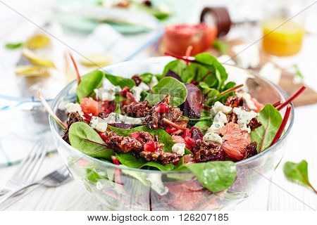 Composition of healthy dinner with beet and baby spinach salad , roasted seabass fish, feta cheese, pomergrat and citrus vinaigrette dressing. White wood background