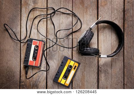 Retro cassettes with headphones on wooden table, closeup
