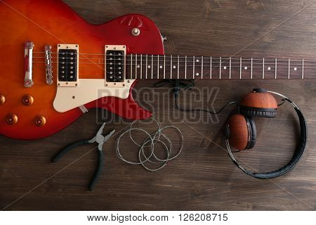 Electric guitar with headphones, pliers and strings on wooden background