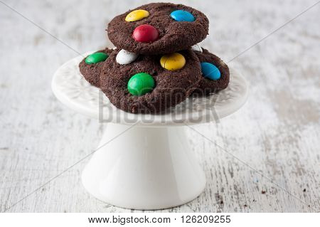 cookies with sugar coated candy on a white wooden background