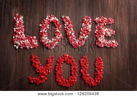 Love you inscription with candies on wooden background