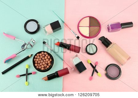 Set with brushes, cosmetics and eyelash curler on bright background