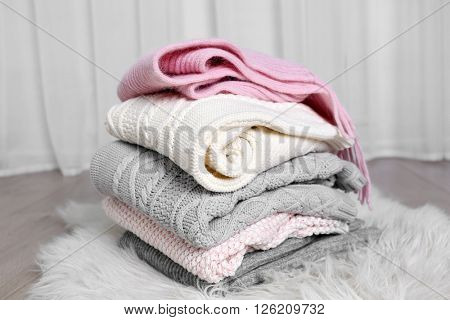 Stack of woolen clothes on white carpet in light interior
