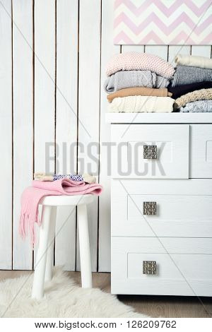 Stacks of woolen clothes on white commode in a light interior