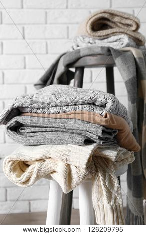 Piles of woolen clothes on wooden stools over white brick wall background