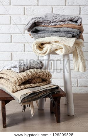 Stacks of woolen clothes on wooden stools over white brick wall background