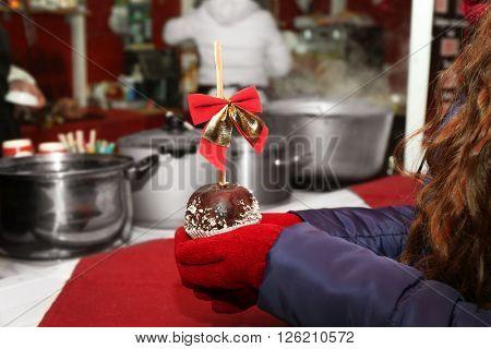 Woman buying apple icing with chocolate at Christmas food kiosk