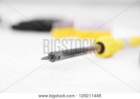 Yellow soldering iron on blurred white background