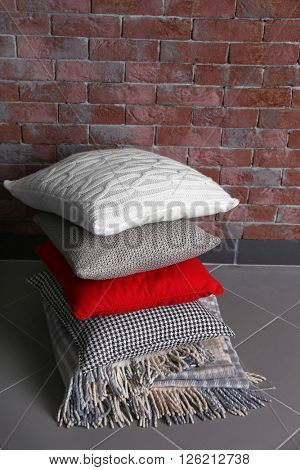 Multicoloured pillows on a brick wall background