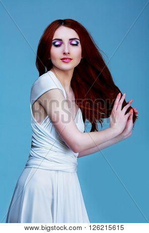 beautiful model with long red hair and colorful makeup, against studio background