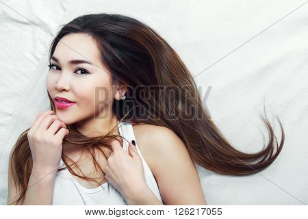 beautiful young asian woman in bed in the interior, top view
