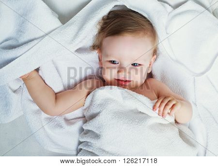 one year old baby in bed with a towel after taking a bath