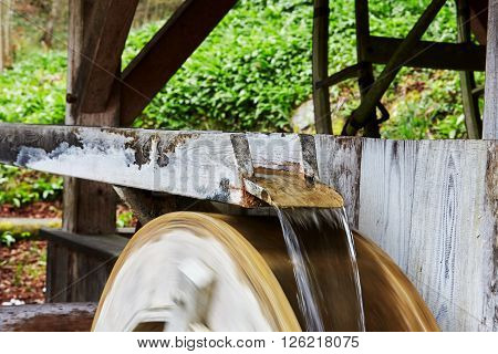 Water running over the turning wheel of a mill