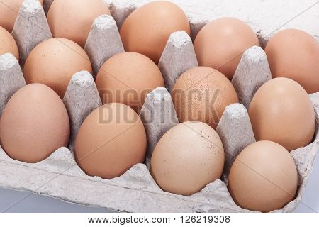 Close up of fresh brown eggs in a cardboard tray