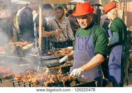 KYIV, UKRAINE - APR 17: Barbecue cook preparing meat outdoor during Street Food Festival on April 17, 2016. Kiev is the 8th most populous city in Europe.