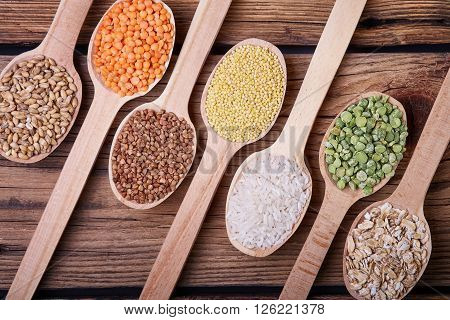 .Grains in the spoon, a wooden spoon, a range of cereals, a table of old wood, the grain harvest, organic food, cereal close-up, texture of old wood, kitchen utensils, healthy food.