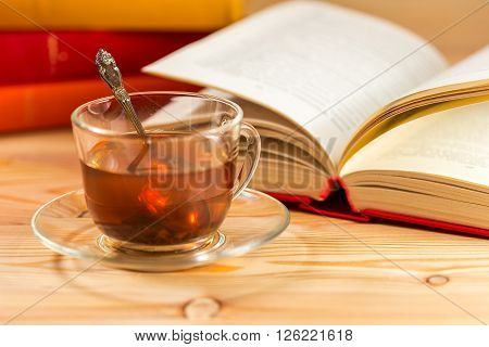 Open book and glass cup of tea and a stack of books with colorful covers.