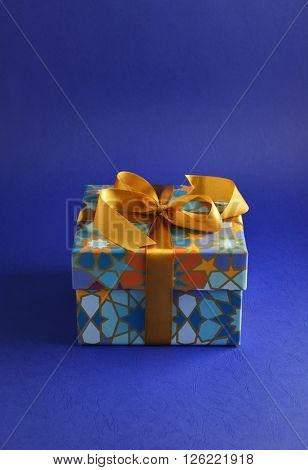 Eid festive gift. A closed gift box with islamic motif pattern and golden ribbon.